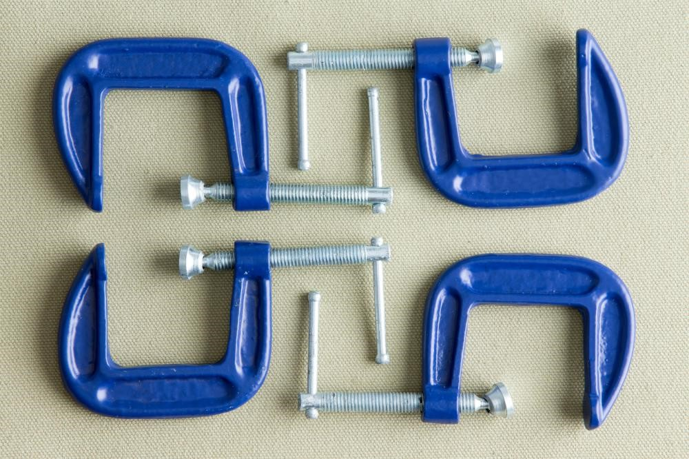 Four blue steel g clamps y arranged on a table.