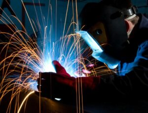 A professional welder performing metal fabrication work on a steel sheet.